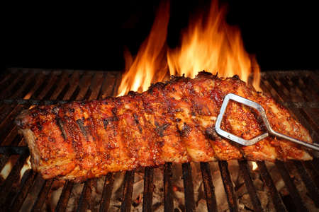 caliente: BBQ asado marinado Baby Back Ribs de cerdo Close-up en caliente Flaming Grill Antecedentes