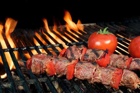 BBQ Beef Shish Kebabs Close-up On The Hot Charcoal Grill With Bright Flames Of Fire On The Isolated Black Background 版權商用圖片