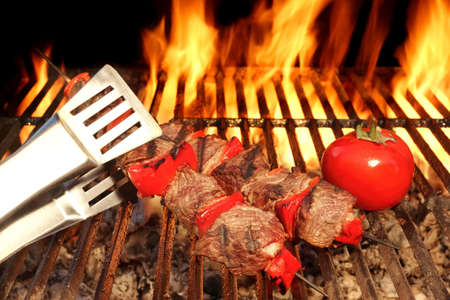 kebob: Tongue Hold BBQ Beef Shish Kebab With Vegetables On The Hot  Flaming Cast Iron Grill Close-up