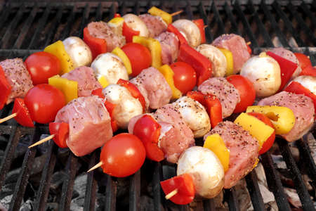 barbequing: Pork And Vegetables Skewers Cooking On BBQ Grill. Good Lunch For Outdoor Summer Barbecue Party Or Picnic Stock Photo