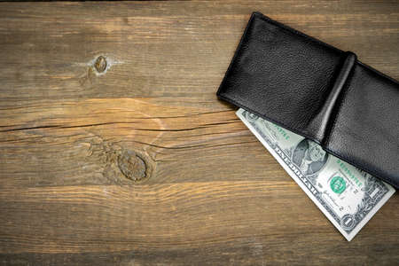 black money: Open Male Black Leather Wallet With USA One Dollar Bill On Old Rough Brown Wood Background With Copy Space Stock Photo
