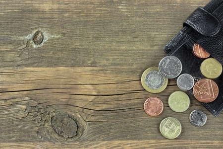 コピー領域に古い大まかな茶色ウッドの背景に英国の異なるコイン付きオープン男性黒レザー ・ ウォレット