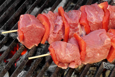 kebob: Raw Beef Kebabs Mixed With Vegetables On The Hot BBQ Grill Background Close-up