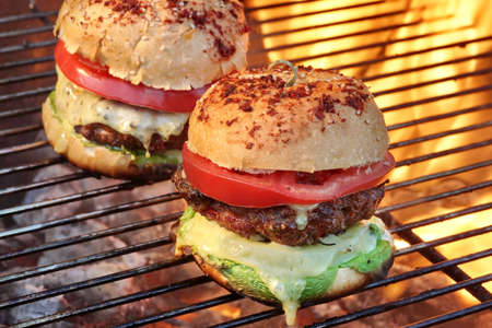 Closeup of Homemade Burgers On Hot BBQ Charcoal Grill With Flames In The Background