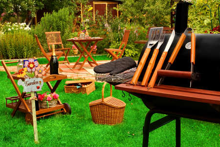 Outdoor Wooden Furniture, Picnic Hamper Basket, BBQ Grill With Tools, Sign Garden, Wine Glasses On The Table, Plants, Trees and House In The Background. Backyard  BBQ Grill Party Or Picnic Concept