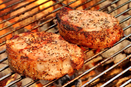 Two Pork Steak Close-up On The BBQ Flaming Charcoal Grill Background