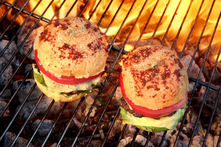 beefburger: Closeup of Homemade Burgers On Hot BBQ Charcoal Grill With Flames In The Background