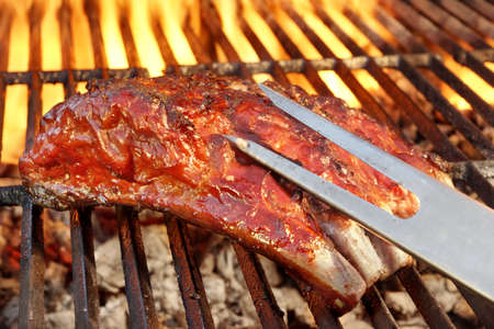 spare ribs: Tasty Smoked Pork Spare Ribs On The Hot Flaming  Barbecue Charcoal Grill Stock Photo