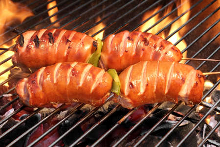 cook out: Close-up Of Four Fatty  Sausage On The Hot BBQ Charcoal Grill And Flames In The Background