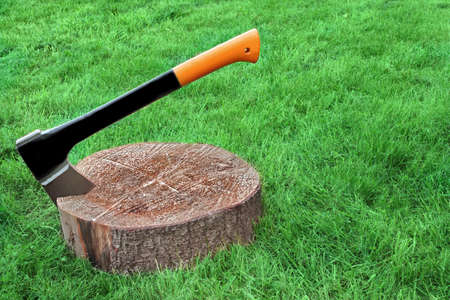 splitter: Modern Axe Or Wood Splitter Set In Chopping Block Close-up Grass On The Background With Copy Space Stock Photo