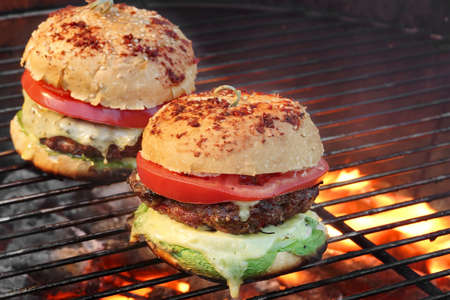 classic burger: Closeup of Homemade Burgers On Hot BBQ Charcoal Grill With Flames In The Background