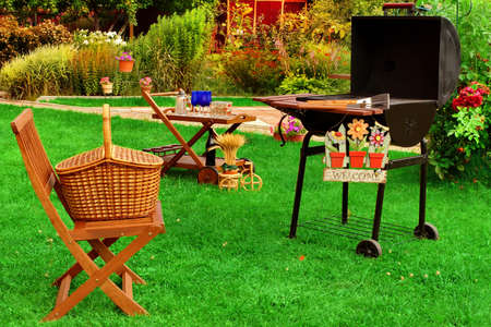 Garden Wooden Furniture, Picnic Hamper Basket, BBQ Grill, Sign Welcome, Wine Glasses On The Table, Plants, Trees and House In The Background. Backyard  BBQ Grill Party Or Picnic Concept