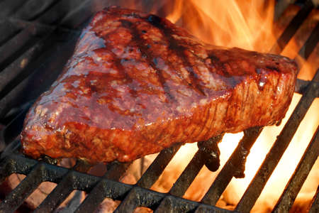 charcoal grill: Beef Steak On The BBQ Flaming Charcoal Grill Close-up Stock Photo