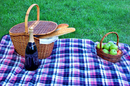 picnic cloth: Picnic Hamper, Wicker Basket With Fruits, Champagne Wine Bottle on The Blanket Close-up. Green Park Lawn On The Background