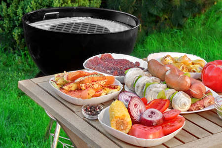 backyards: Close-up View On Wood Picnic Table  With Different Cookout Food For Summer BBQ Family Party On The Backyard And Empty Barbecue Grill Appliance On The Green Grass And Plants Background