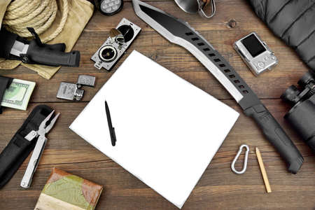 large group of items: Rough Wood Desktop With  Objects For Travel, Expedition, Exploration Or Hike. Camera, Notebook, Knife, Machete, Compass, Wallet, Raincoat, Binoculars, Rope, Backpack, Led Torch, Multifunctional Tools