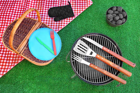 Overhead View Of Red Picnic Tablecloth, Plate, Fork, Knife, Barbecue Tools, Bucket With Charcoal Briquettes, BBQ Grill Appliance On The Summer Green Lawn Background