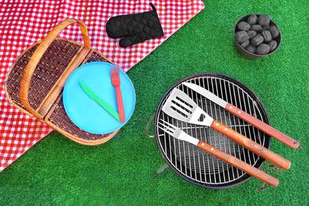 Ovanifrån av Red picknick duk, plåt, gaffel, kniv, grill verktyg, hink med kol Briketter, grill Appliance On The Summer Green Lawn Bakgrund