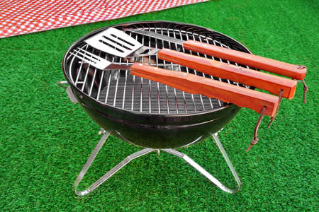 Summer BBQ Grill Party Or Picnic Concept. Barbecue Charcoal Kettle Grill With Tools, Picnic Red Tablecloth Are On The Bright Green Grass Background