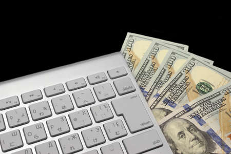 fraudster: USA Dollar Bills And Wireless Keyboard Isolated On Black Background