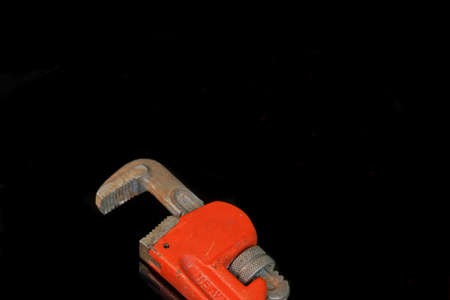 movable jaw: Large Adjustable Wrench With Red Handle Isolated On Black