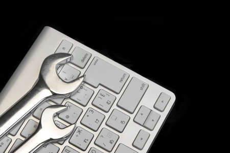 Chrome Plated Wrenches And Wireless Keyboard Isolated On Black Glass Background With Reflection. Remote Assistance Or Technical Support Or Repair Service Or Bug Fix Or Business Solutions Concept