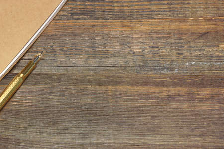 old desk: Notepad With Real 24k Gold Fountain Pen On The Old Rough Wooden Table Background Stock Photo