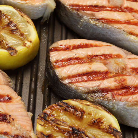 cast iron pan: Grilled Salmon Steaks And Lemon On The Cast Iron Pan Stock Photo