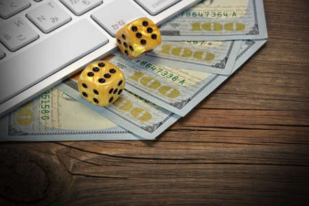 double the chances: Computer Keyboard, Gaming Dices And USA Dollar Cash On The Rough Brown Wood Background. On Line Gambling Game Concept Stock Photo