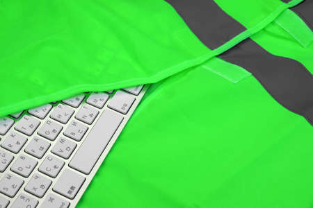 safety vest: Keyboard In The Green Reflective Safety Vest  Technical Or Road Assistance Or Professional Help Concept With Copy Space