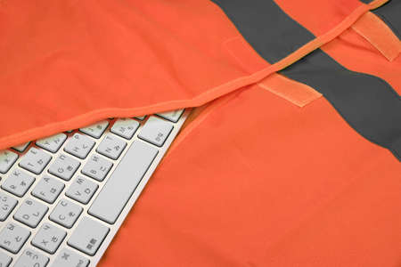 road assistance: Keyboard In The Orange Reflective Safety Vest  Technical Or Road Assistance Or Professional Help Concept With Copy Space