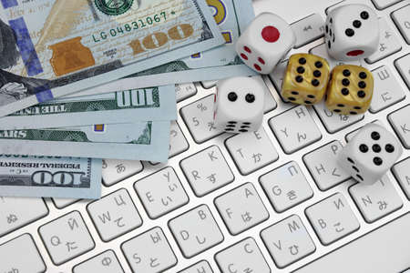 double the chances: Computer Keyboard Close-up,  Gaming Dices And USA Dollar Cash.  On Line Gambling Game Concept Stock Photo