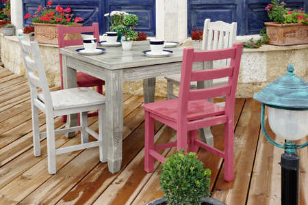 dining table and chairs: Vintage White Wooden Dining Table And Chairs On The Wet Wood Patio Floor Near Rustic Blue House Wall Stock Photo