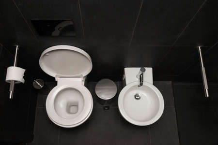 a toilet seat: Top View Of Modern Toilet Bowl, Bidet And Toilet Paper In The Black Room