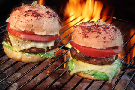 cheeseburgers: Homemade Cheeseburgers On The Hot Flaming BBQ Grill Close-up