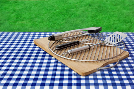 Picnic Table Covered Checkered Blue White Tablecloth And BBQ Grill With Tools Kit, Park Lawn In The Background