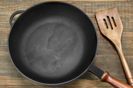nonstick: New Clean Empty Cast Iron Frying Pan And Spatula Overhead View On The Wood Background