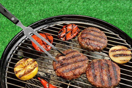 party food: BBQ Hamburgers On The Hot Charcoal Grill. Cookout Concept. Good Snack For Summer Outdoor Party Or Picnic.Backyard Lawn In The Background.