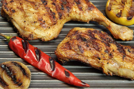 griddle: BBQ Marinated Chicken Legs Grilled On A Grill Pan, Top View Closeup Stock Photo