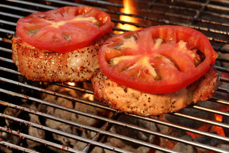 cook out: Pork Loin Pepper Steaks On The Hot BBQ Grill With Vibrant Flames In The Background, Close Up Stock Photo