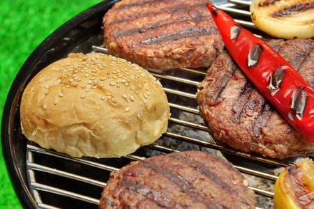 lawn party: Barbecue Burgers On The Hot Charcoal Grill. Cookout Concept. Good Snack For Summer Outdoor Party Or Picnic.Backyard Lawn In The Background. Stock Photo