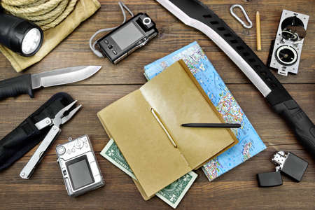large group of items: Survival Kit Laid Out On The Rustic Rough Wood Floor. Items Include,  Blank Notebook, Money, Pen, Flashlight, Knife, Machete, Rope, Bag, Tools
