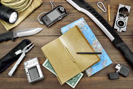 kompas: Survival Kit stanoven na rustikální Rough dřevěná podlaha. Položky zahrnují, Blank notebook, peníze, pero, baterku, nůž, Machete, Rope, Bag, nástroje