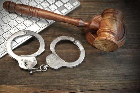 escena del crimen: Concepto delincuencia en el ciberespacio, teclado del ordenador jueces martillo Y el Real esposas en el áspero Marrón Madera Mesa
