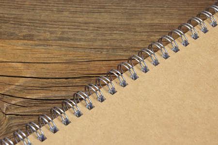 espiral: Cerrado Notebook Bound Espiral Con Textura del fondo de la cubierta de papel de Brown en la madera rústico tabla, vista superior