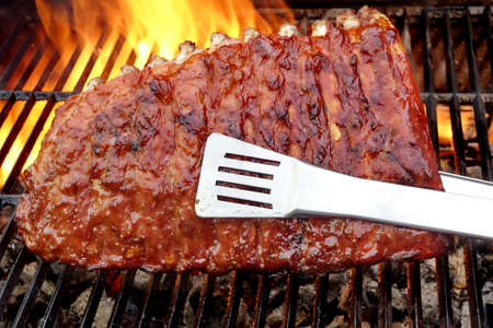 Baby Back Or Pork Spareribs BBQ Roasted On The Hot Flaming Charcoal Grill