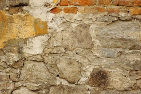old building facade: Old Building Facade With Cracked Plaster And Damaged Bricks Background Texture Stock Photo