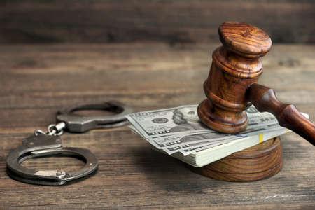 USA Dollar Cash Money, Real handboeien en Rechter Hamer Op Ruwe Houten Achtergrond. Concept Voor Arrestatie, corruptie, borgtocht, Criminaliteit, omkopen of fraude. Stockfoto