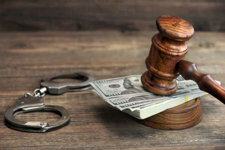 justiz: USA-Dollar-Geld-Bargeld, Echthandschellen und Richter Hammer auf rauem Holz Hintergrund. Konzept für Festnahme, Korruption, Bail, Kriminalität, Bestechung oder Betrug.