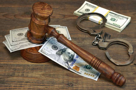 restraints: Dollars Cash, Real Handcuffs And Judge Gavel On Rough Wood Background. Concept For Arrest, Corruption, Bail, Crime, Bribing or Fraud.